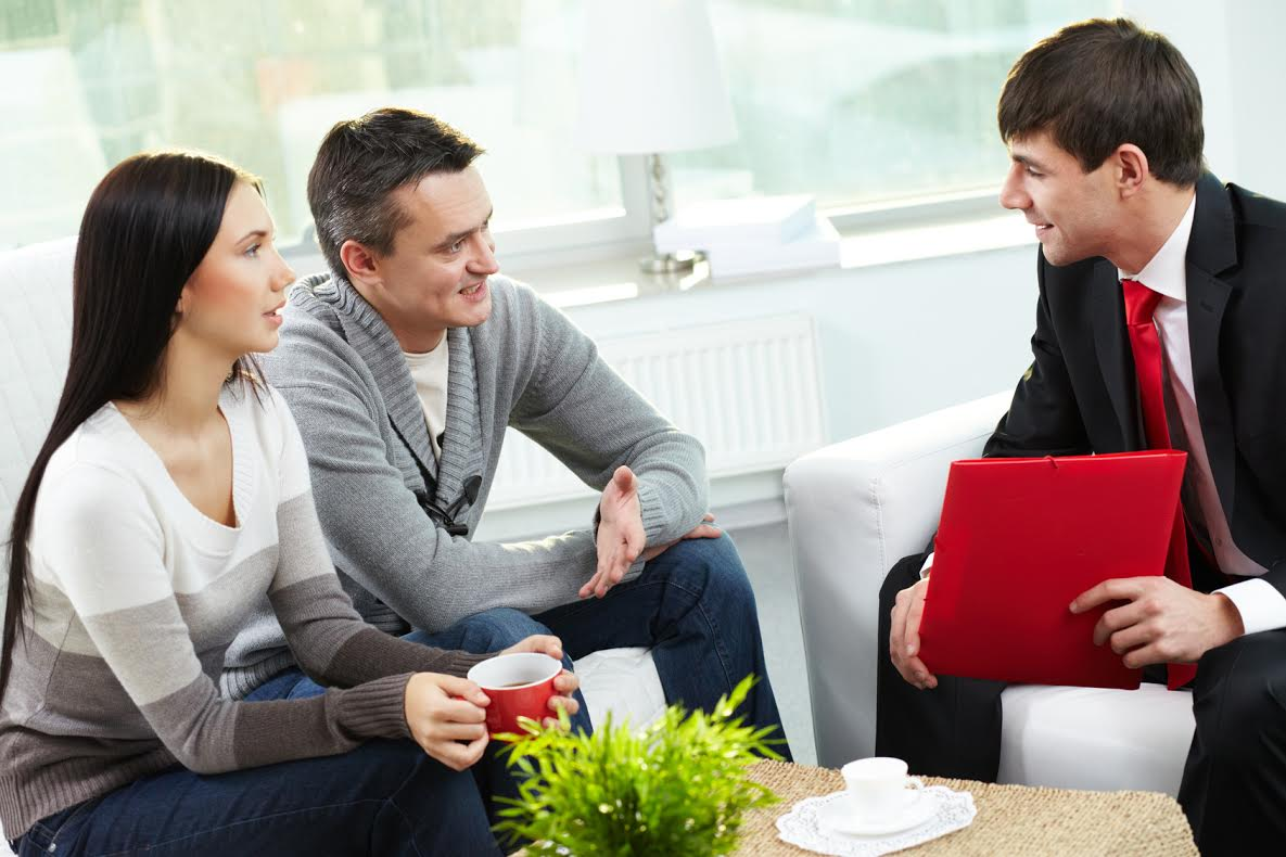 Portrait of modern couple talking to manager while discussing conditions of mortgage